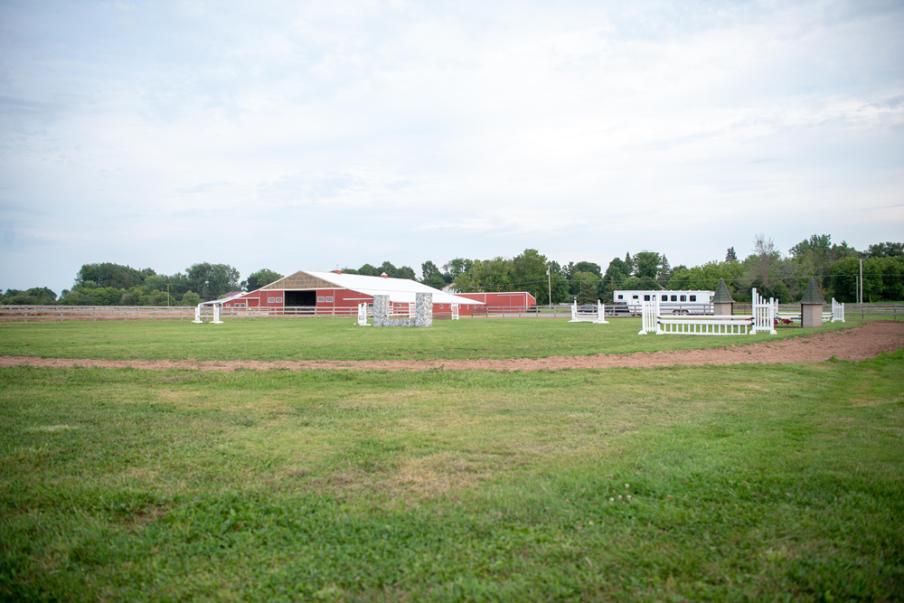 Outdoor arena with hunt course with barn in the background
