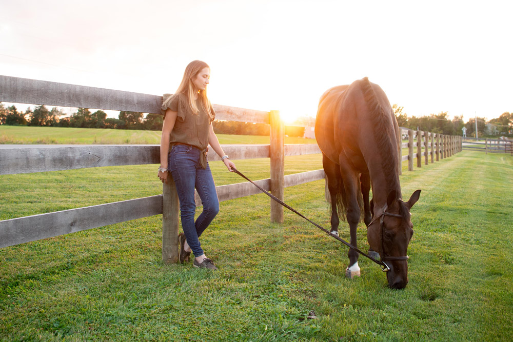 Maddy Keyes leans against fence while Classic Circle grazes
